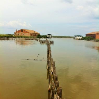 """Im Hintergrund zwei der """"Casoni"""", in denen die Fischer von Comacchio während ihrer tagelangen Aalfangtouren übernachteten"""